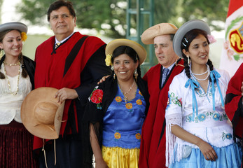 Peru's President Garcia and Colombia's President Uribe pose with Andean women while wearing traditional Andean costumes during a photo session after the Andean Community summit in Tarija
