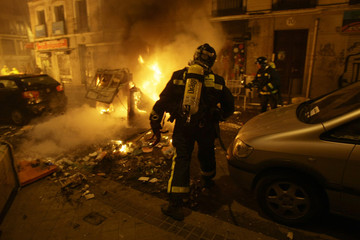A fireman tries to control a fire during clashes between riot police and anti-fascists in Madrid