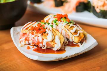 Sushi nigiri tamago with salmon on dish.