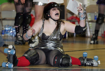 Cosmonaughties Raquel Squelch reacts after taking a hit from one of the Wicked Pissahs during second period of Boston Derby Dames Roller Derby Bought in Boston