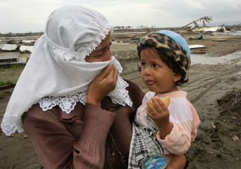 An Acehnese mother holds her son as she talks about a second son killed by Indian Ocean tsunami ...