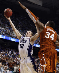 Duke University forward Kyle Singler shoots around University of Texas center Dexter Pittman during the second round of their NCAA basketball game in Greensboro