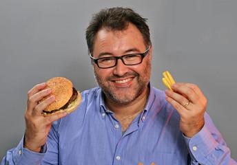 Hombre gordo feliz comiendo hamburguesa y patatas fritas.