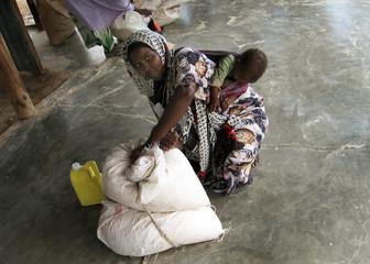A Somali refugee mother fastens her food ration kit at a distribution centre in northeastern Kenya
