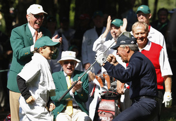 Gary Player of South Africa celebrates with Jack Nicklaus and his grandson William after hitting his second tee shot into the cup for a par after his first shot went into a pond during the annual Par 3 tourament