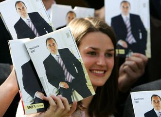 Scottish National Party supporter is surrounded by booklets with party leader Salmond on the front cover after the launch of the party manifesto in Edinburgh