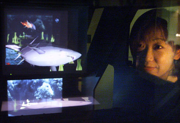 A JAPANESE WOMAN LOOKS INTO NEW 3D IMAGE DISPLAY BOX AT UNVEILING IN TOKYO.