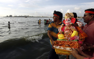 Devotees carry idol of Hindu elephant god Lord Ganesha for immersion in Mumbai
