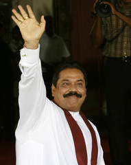 Sri Lankan President Mahinda Rajapakse waves to the media after he handed in his applications for the January 26, 2010 presidential elections, in Colombo