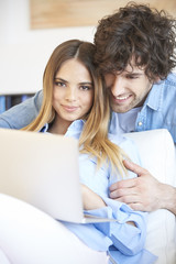 Spend time together. Shot of a lovely young couple sitting at home and relaxing.  Smiling young woman browsing on the internet at laptop with her handsome boyfriend.