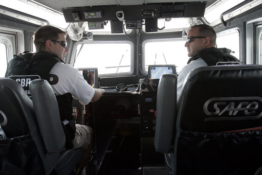 U.S.Department of Homeland Security Customs and Border Protection Air and Marine Operations Agent's Scott Leach and Tom Pope talk to each other as they ride along Lake Erie in a patrol boat in Gibralter, Michigan
