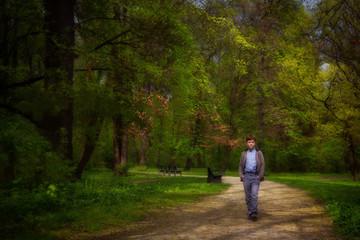 The boy walks in garden