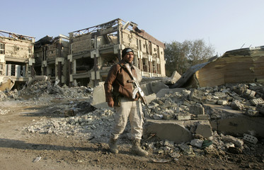 An Iraqi security personnel patrols at the site of a bomb attack in central Baghdad