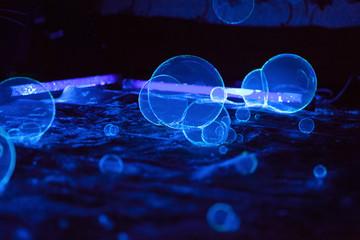 Soap bubbles on dark background in fluorescent light