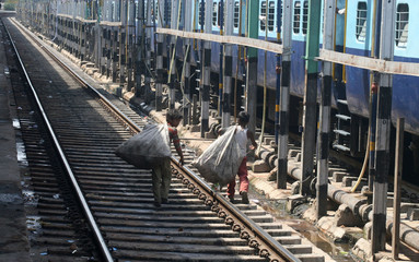 Rag pickers walk along a railway track at the railway station in Allahabad