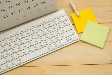 top view. calendar putting on top of keyboard and have post-it note putting on beside. wooden are background. this image for business and education concept