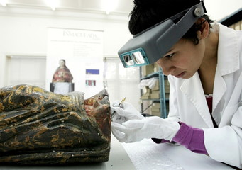 An art conservation expert extracts a moth from an 18th century colonial wood carving of the Virgin ..