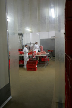 Workers pile meat on sticks in a Kebab production hall in Berlin