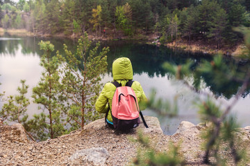 Hipster young girl with backpack enjoying the view of the lake on peak of foggy mountain among the pine forest. Tourist traveler.