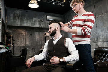 Hairdresser man shaves a client with a beard in a barbershop