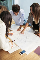 Young architects, engineers with customers during a meeting in office. They show and indicate the project