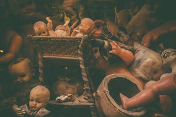 Creepy broken dolls in parts. Vintage retro edit.