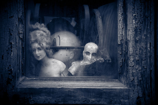 Creepy old vintage nostalgic dolls and figurines, looking out through cracked textured dirty window.