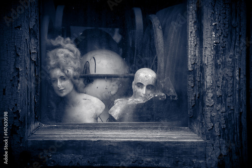 Creepy Old Vintage Nostalgic Dolls And Figurines Looking Out Through Cracked Textured Dirty Window