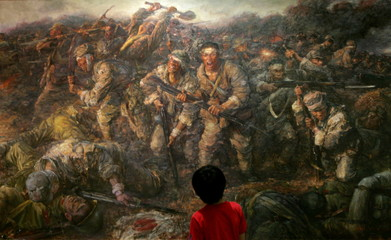 A child looks at a painting depicting scenes from a Sino-Japanese battle during World War II at an e..
