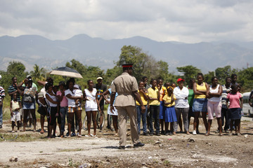 Residents of Rose Town, stand at distance as Britain's Prince Charles and Camilla, Duchess of Cornwall, visit suburb in Kingston