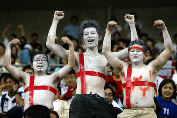 Three Japanese soccer fans show off their chests painted like a flag of St. George before the start ..