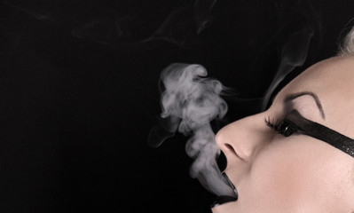 pretty alternative woman smoking on black background