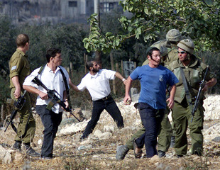 ISRAELI SETTLERS RESTRAINED BY ISRAELI SOLDIERS AS THEY THROW STONES TOWARD PALESTINIANS IN NABLUS.