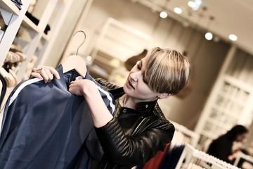 Junge, blonde Frau beim Shopping in einem Modehaus, betrachtet ein Oberteil
