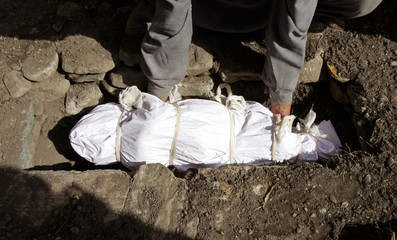 The body of a young girl is buried after it was recovered from the rubble her house in Bandi Sarie