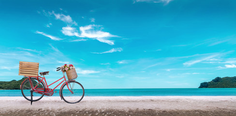 Red vintage bicycle on white sand beach over blue sea and clear blue sky background, spring or summer holiday vacation concept.