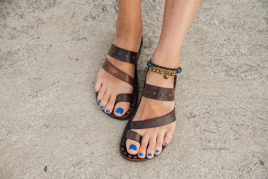 Legs of a girl with a blue pedicure in leather sandals on the pier