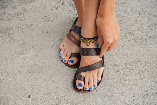 Legs of a girl with a blue pedicure in leather sandals on the pier.