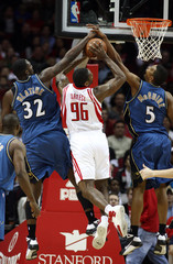 Washington Wizards forwards Andray Blatche and Dominic McGuire team up to block the shot of Houston Rockets forward Ron Artest during their NBA basketball game in Houston