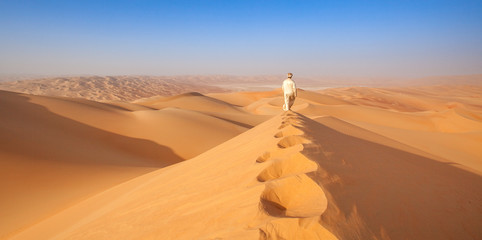 arab man in Kandoura walking over a Dune in the arabian Desert Wall mural