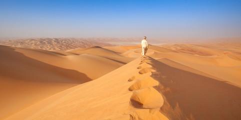 arab man in Kandoura walking over a Dune in the arabian Desert Fotoväggar