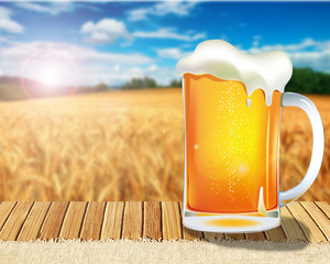 a good glass of beer on table on bright background of a wheat field
