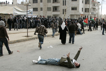 Protester gestures while lying on the floor during as riot police clash with protesters in Amman