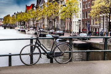 Black bicycle on the bridge on the canal of Amsterdam, Netherlands