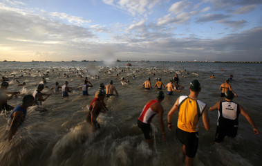 Competitors enter the water during the start of the Aviva Ironman 70.3 triathlon in Singapore