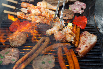 Delicious assortment of meat and vegetables grilling on a BBQ with pork sausages, chops, skewers with mixed kebabs