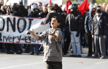A boy shouts at riot police during a demonstration in front of the Greek parliament building in Athens