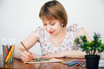 Young woman drawing at the desk