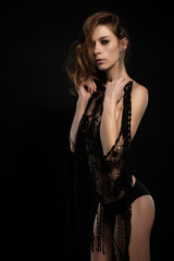 portrait of sexy brunette with long hair in shorts that keeps black lace jacket