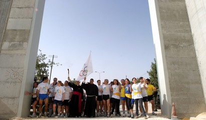 Palestinian and international runners run towards the checkpoint between the West Bank city of ...